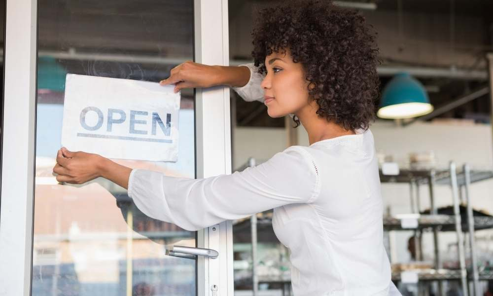 business-owner-placing-open-sign-peo-company